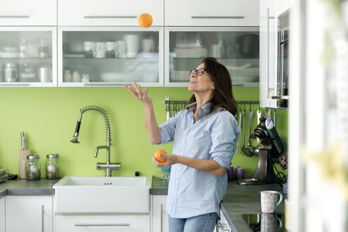 Mature woman juggling with oranges in kitchen at home - FLLF00092