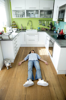 Mature woman lying on the floor in kitchen at home - FLLF00095