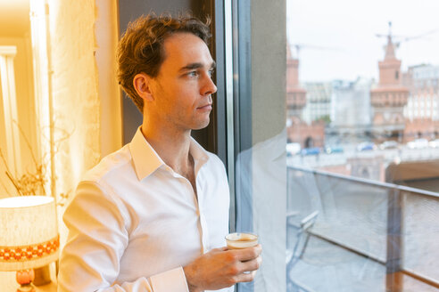 Mid adult businessman looking through office window while taking coffee break - CUF50151