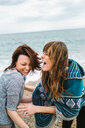 Two young adult female friends laughing on beach, Barcelona, Spain - CUF50193
