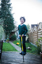 Boy jumping on pogo stick in garden - CUF50205