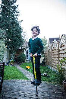 Boy jumping on pogo stick in garden - CUF50205