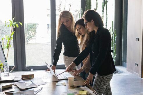 Businesswomen using laptop in office - CUF50217