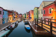 Moored boats on canal lined with colourful stucco houses, shops and footbridge at dusk, Burano Island, Venetian Lagoon, Venice, Veneto, Italy - CUF50235