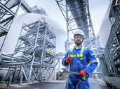 Composite image of engineer with climbing gear in biomass plant - CUF50268