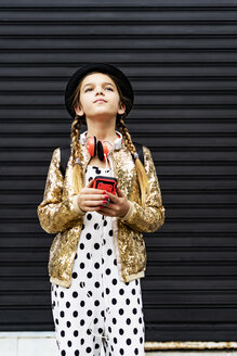 Portrait of girl with smartphone wearing hat, golden sequin jacket and polka dot jumpsuit thinking - ERRF00889