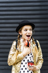 Portrait of astonished girl with headphones and smartphone wearing hat and golden sequin jacket - ERRF00895