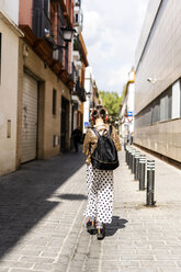 Back view of girl with backpack and headphones walking along the street - ERRF00898