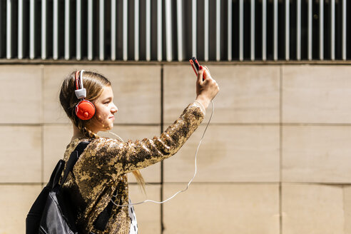 Girl with backpack and headphones taking selfie with smartphone - ERRF00901