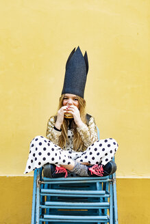 Portrait of girl wearing black crown sitting on stack of chairs eating Hamburger - ERRF00904