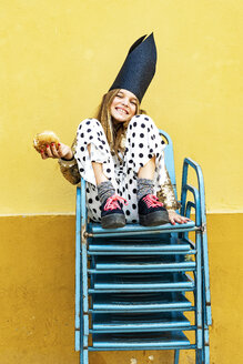 Portrait of laughing girl wearing black crown sitting on stack of chairs eating Hamburger - ERRF00913