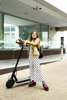 Portrait of smiling girl with E-Scooter wearing golden sequin jacket and polka dot jumpsuit - ERRF00928
