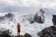 USA, Hawaii, Big Island, Laupahoehoe Beach Park,Man taking pictures of breaking surf at the rocky coast - FOF10569