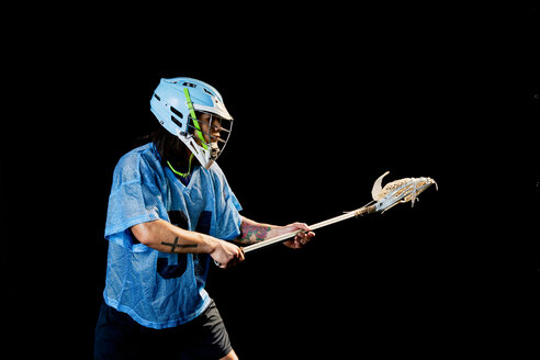 Young male lacrosse player poised with lacrosse stick, against black background - ISF21070