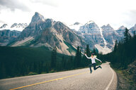 Woman jumping in mid air on road, Jasper, Canada - ISF21094