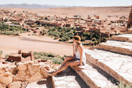 Woman enjoying view on steps, Ouarzazate, Souss-Massa-Draa, Morocco - ISF21106
