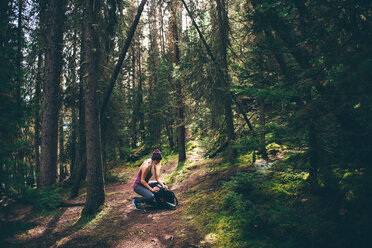 Hiker checking backpack in forest, Johnston Canyon trail, Banff, Canada - ISF21115