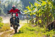 Biker exploring countryside, Nan, Thailand - CUF50275