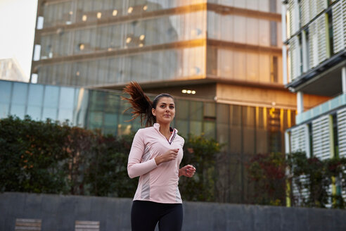 Woman jogging on sidewalk, Barcelona, Catalonia, Spain - CUF50281