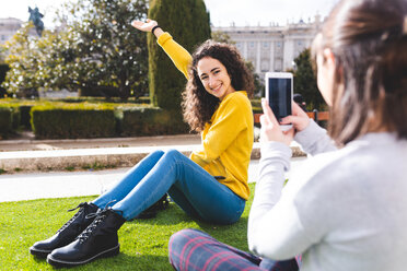 Girlfriends taking photograph in city park, Madrid, Spain - CUF50308