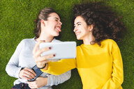 Girlfriends taking selfie on grass - CUF50311