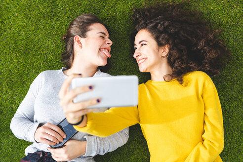 Girlfriends taking selfie on grass - CUF50311