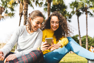 Girlfriends reading message on smartphone in city park - CUF50320