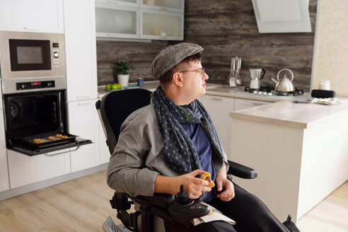 Physically impaired man holding cookie in kitchen - CUF50323