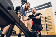 Personal trainer working with man with disability on rowing machine - CUF50335