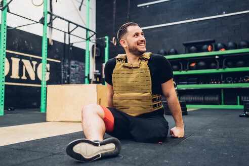 Man with disability sitting on gym floor smiling - CUF50338