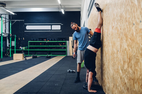 Man with disability doing handstand against chipboard wall - CUF50344