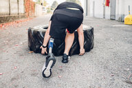 Man with prosthetic leg weight training with giant tyre - CUF50362