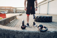 Man with prosthetic leg beside training tyre and kettlebells - CUF50365