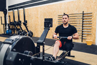 Man with disability using rowing machine in gym - CUF50377