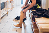 Man with prosthetic leg in gym changing room - CUF50380