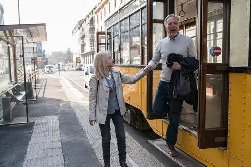 Senior couple getting off tram in city - CUF50407