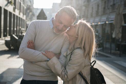 Woman whispering into senior man's ear on street - CUF50422