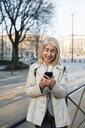 Mature woman using smartphone on sidewalk in city - CUF50428