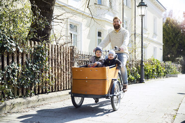 Happy father with two children riding cargo bike in the city - MAEF12831