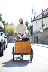 Happy father with two children riding cargo bike in the city - MAEF12834