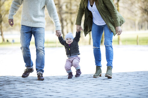 Portrait of happy girl walking hand in hand with parents - MAEF12837