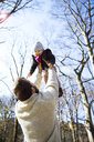 Father lifting up happy daughter in park - MAEF12849