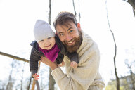 Portrait of happy father holding daughter in park - MAEF12852