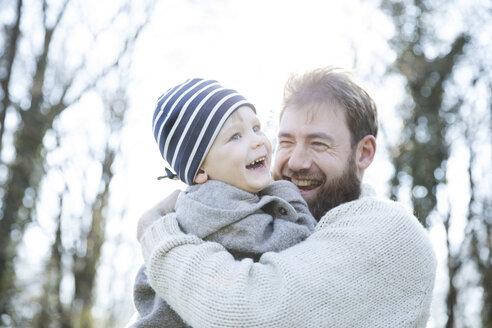 Portrait of happy father carrying son in park - MAEF12858