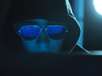 Cyber Crime, reflection in spectacles of virus hacking a computer, close up of face - ABRF00370