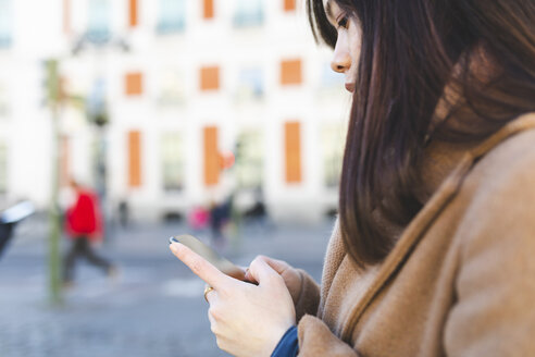Spain, Madrid, close-up of young woman using her smartphone in the city - WPEF01467