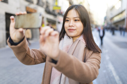 Spain, Madrid, young woman taking photos with a smartphone in the city - WPEF01470