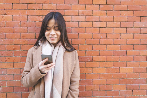 Smiling young woman using cell phone at brick wall - WPEF01473