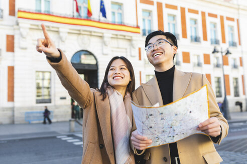 Spain, Madrid, happy young couple with map exploring the city - WPEF01476