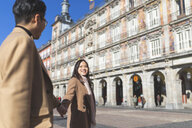 Spain, Madrid, happy young tourist couple holding hands on Plaza Mayor - WPEF01497